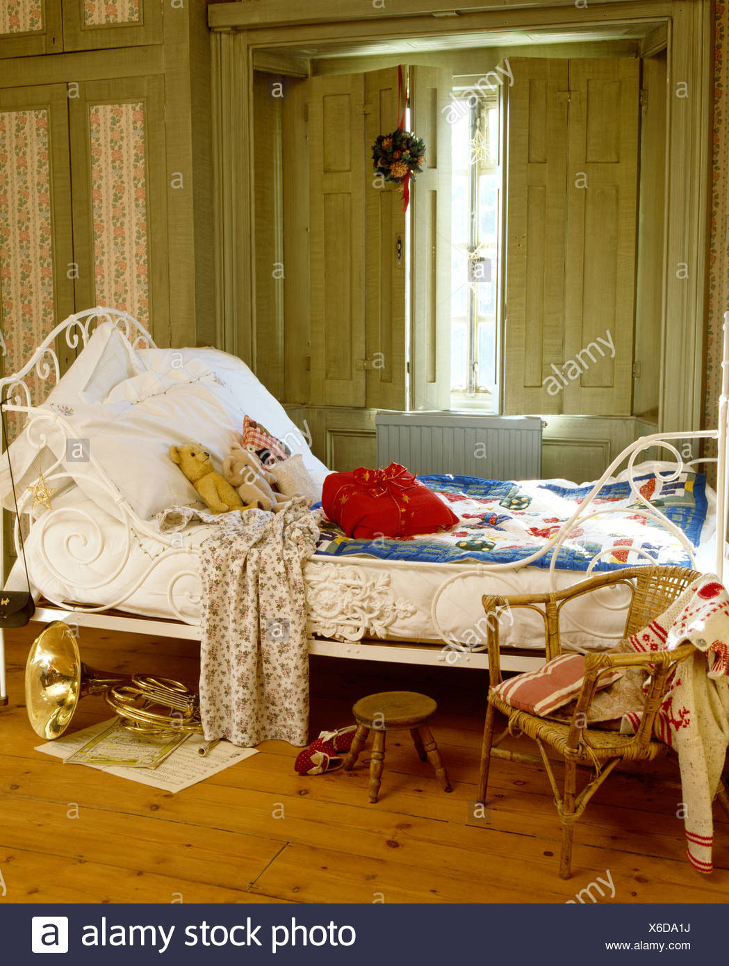Picture of: White Pillows And Blue Quilt On Antique Wrought Iron Bed In Front Of Window With Painted Shutters In Child S Bedroom Stock Photo Alamy