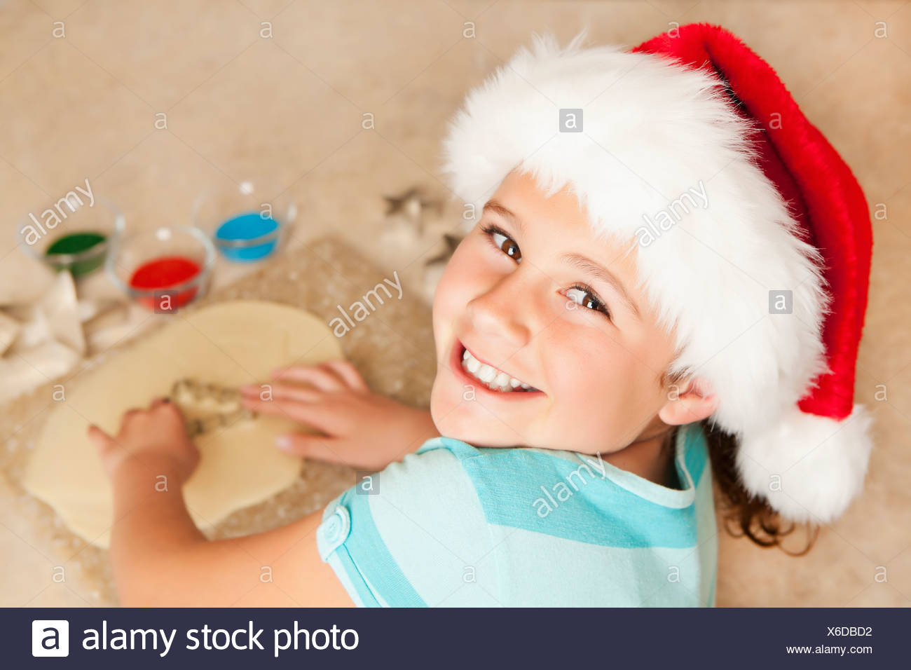 USA, California, Lawndale, Portrait of girl (10-11) wearing santa hat using pastry cutter - Stock Image