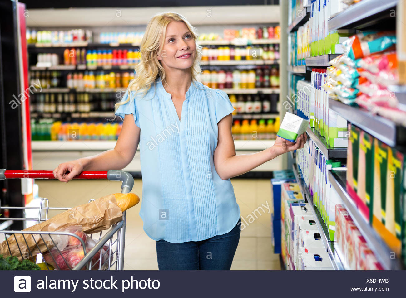 Thoughtful woman holding product Stock Photo
