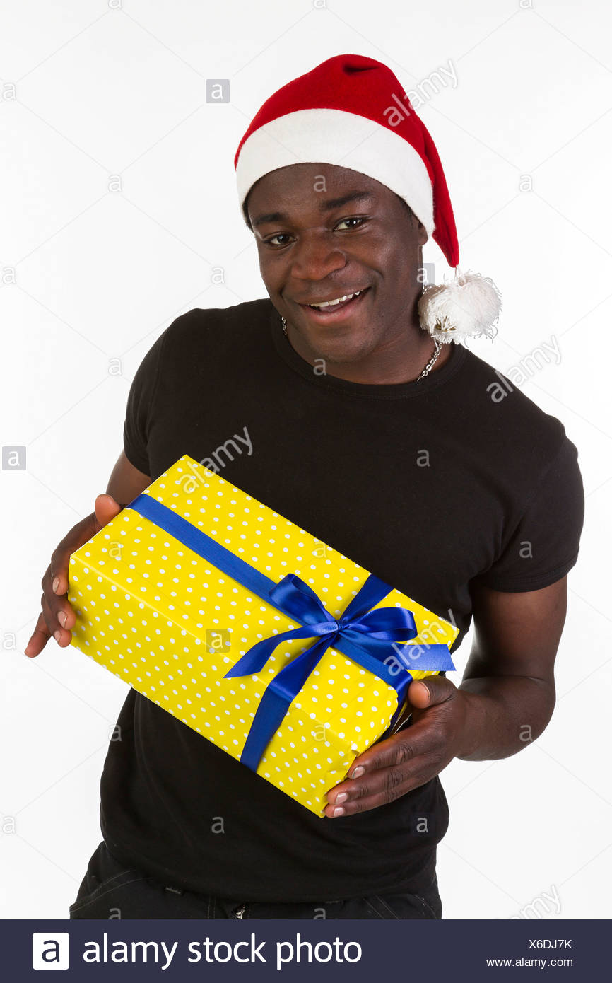 192339d9447f0 Young black man wearing a Santa hat and holding a present - Stock Image