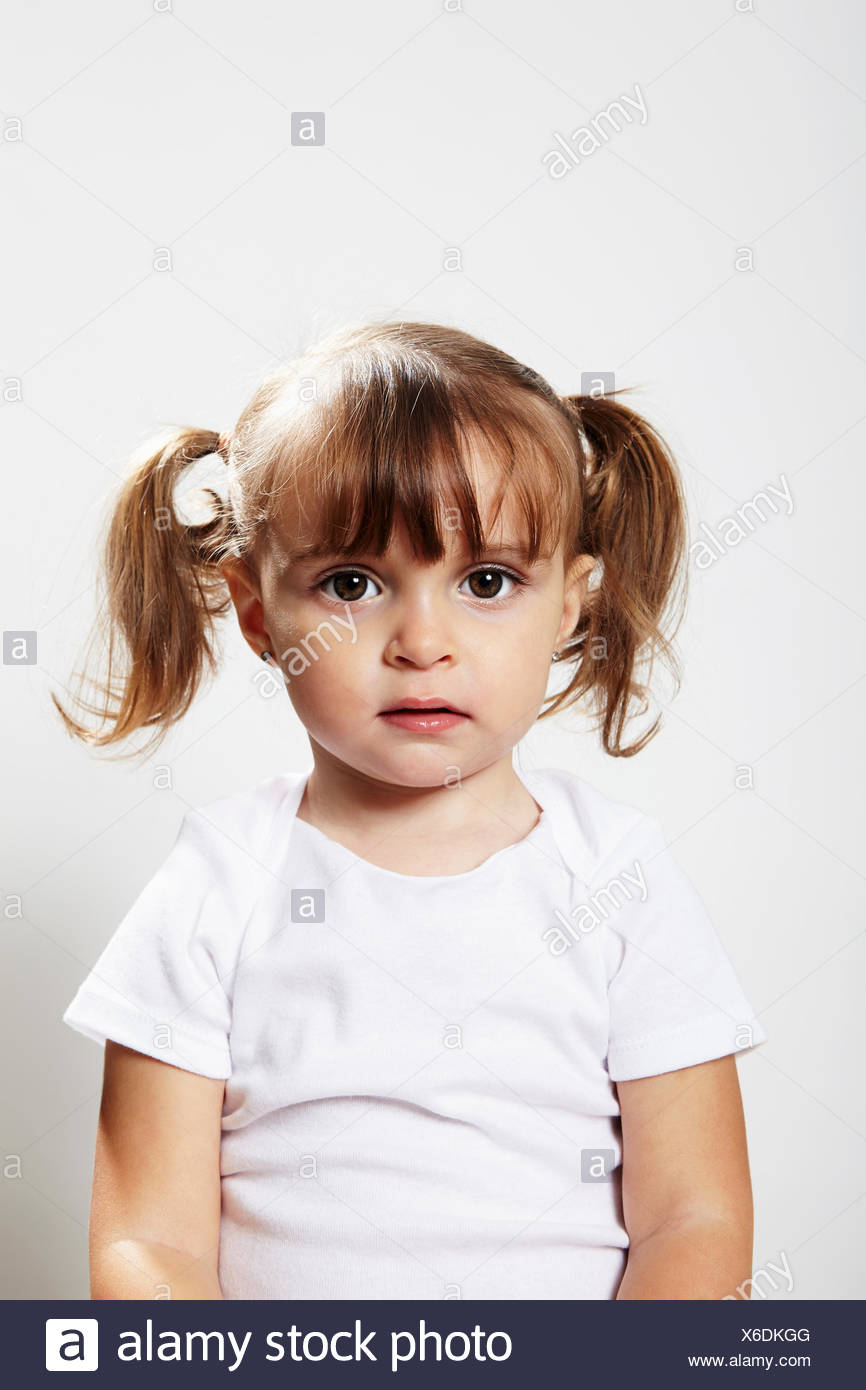 Portrait of young girl with pigtails - Stock Image