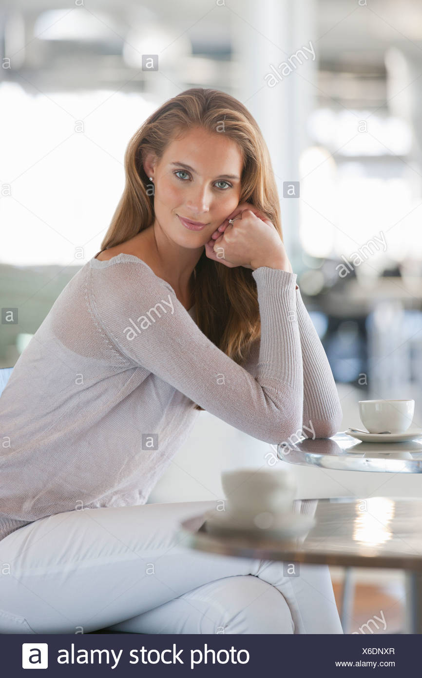 Portrait of confident woman drinking coffee at cafe table - Stock Image