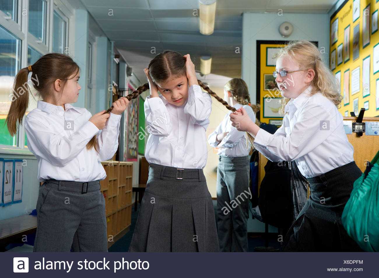 Mean, aggressive school girls teasing and pulling classmates braids - Stock Image