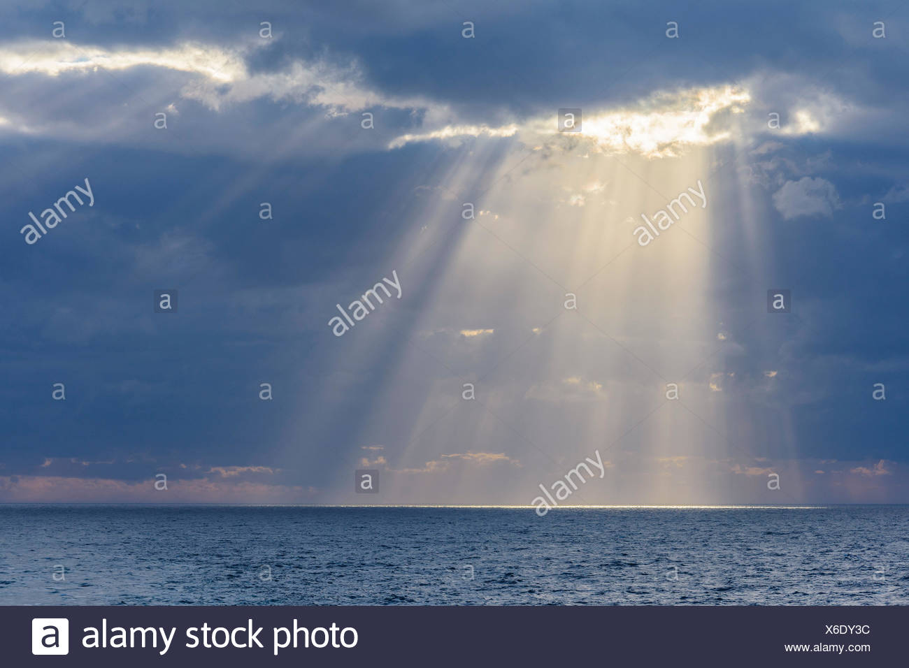 Sun breaks through the clouds with sunrays over sea, North Sea, United Kingdom - Stock Image