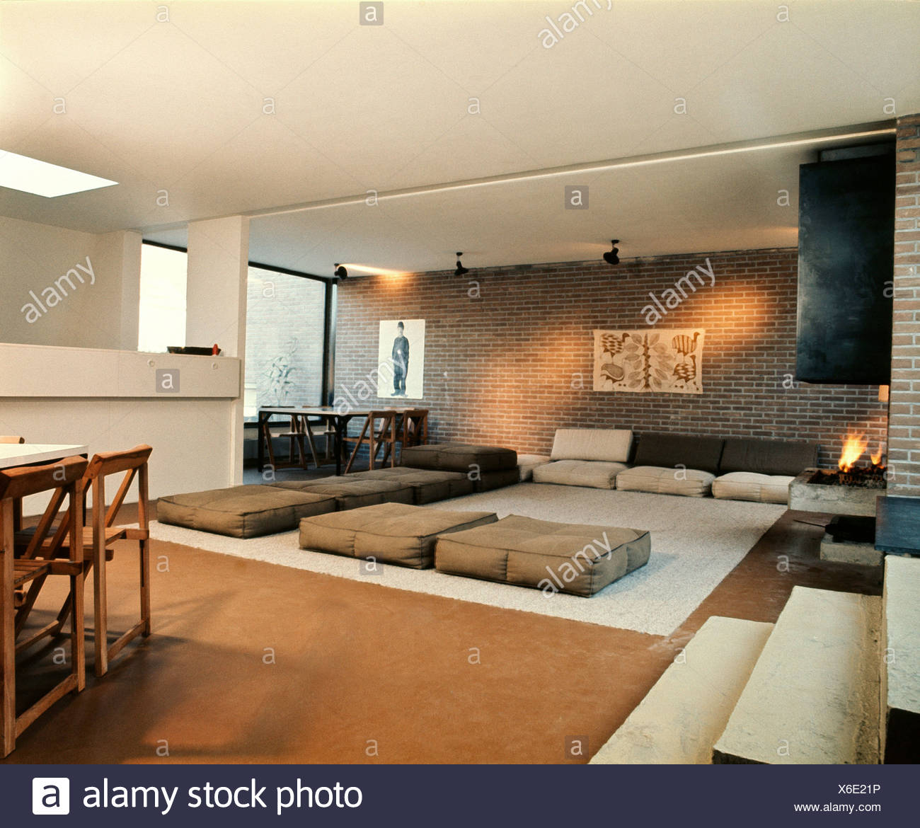 Large Living Dining Room Brick Walls White Ceiling Brown Carpet Grey Rug And Large Square Brown And Grey Flocushions Open Stock Photo Alamy