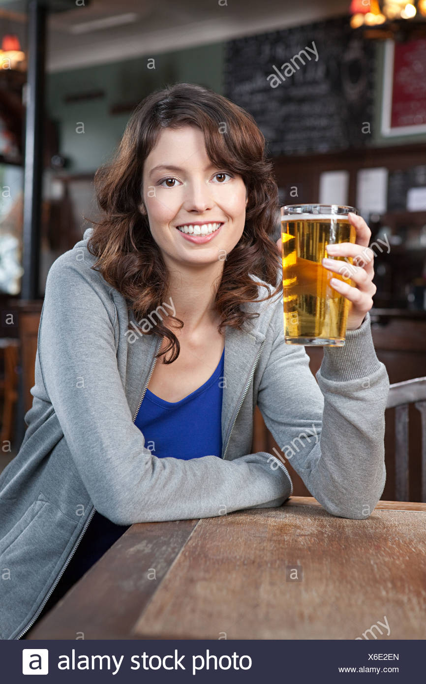 Young woman in bar with pint of beer - Stock Image