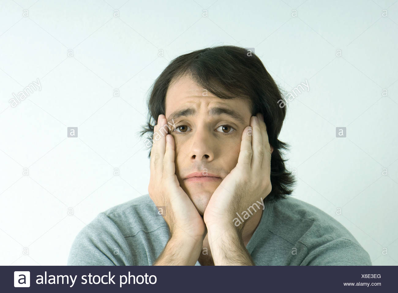 Man holding head in hands, portrait - Stock Image