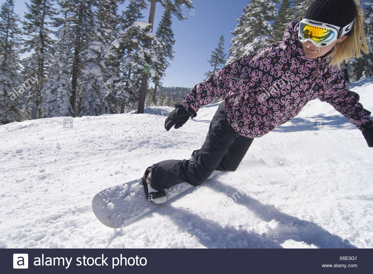 A woman snowboarding on a groomed run at Northstar ski area near Lake Tahoe in California Stock Photo
