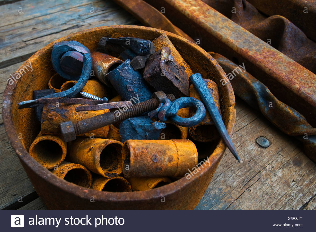 Close-up of a bucket of abandon rusty scrap on wooden surface - Stock Image