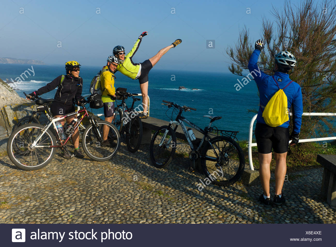 A cyclist does an arabesque on a stone wall above the ocean. - Stock Image