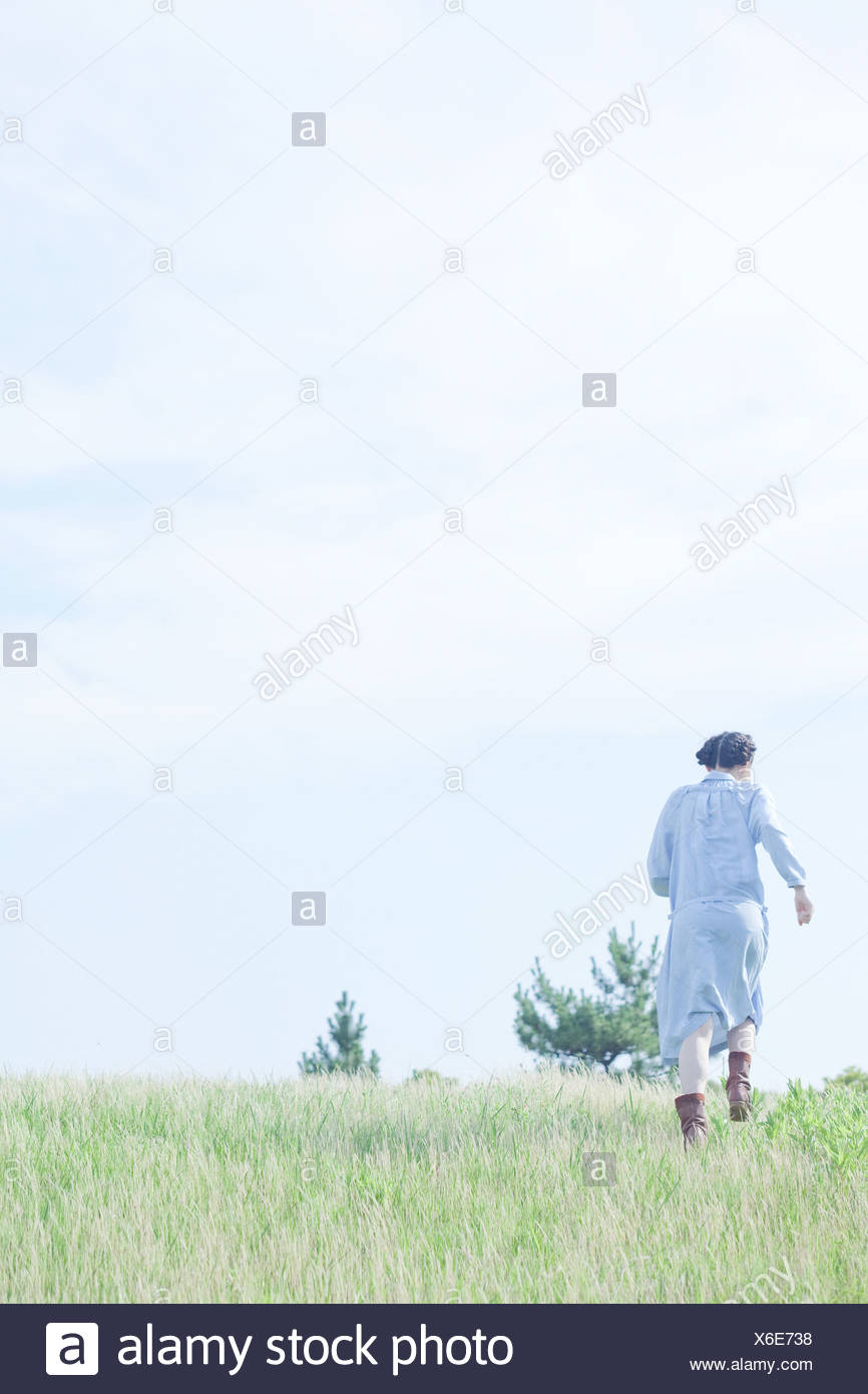 Young woman walking in field, rear view - Stock Image