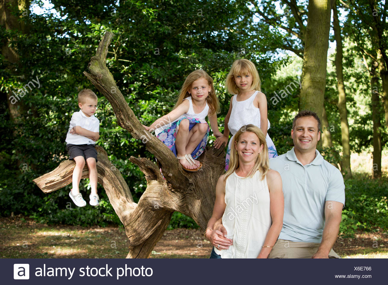 Family with three children by a tree in a forest, posing for a picture. - Stock Image