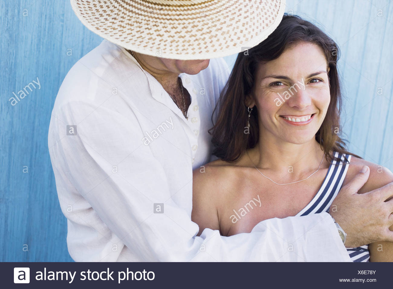 Side profile of a mid adult man embracing a mid adult woman - Stock Image