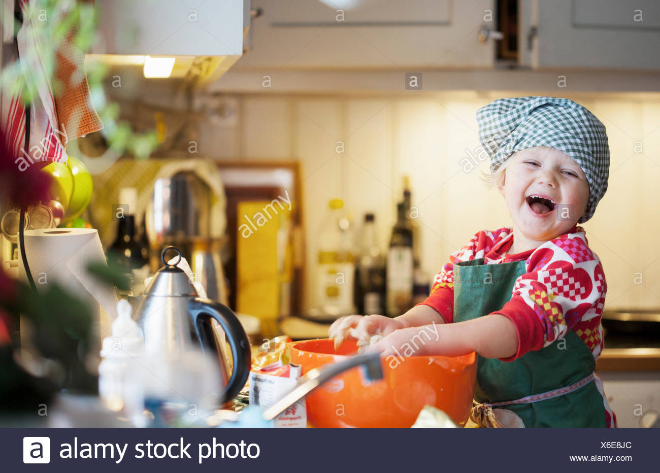 A happy young girl baking in a kitchen - Stock Image