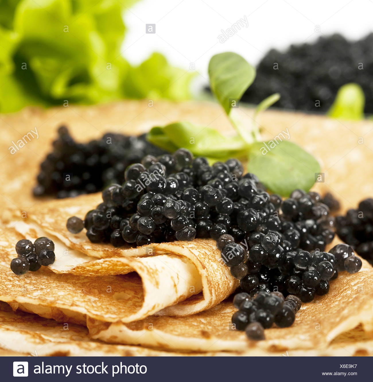 pancake with black caviar and greens - Stock Image
