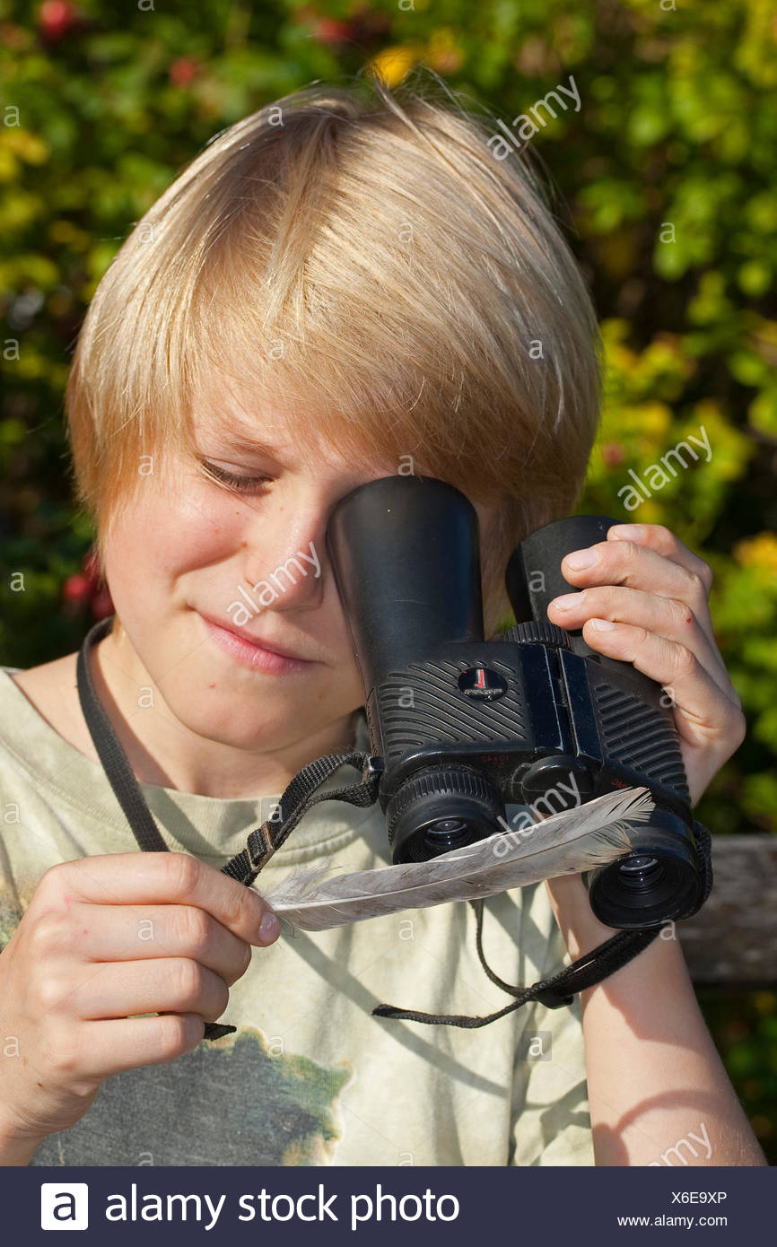 boy using a reversed binocular as a magnifier and looks at a feather, Germany - Stock Image