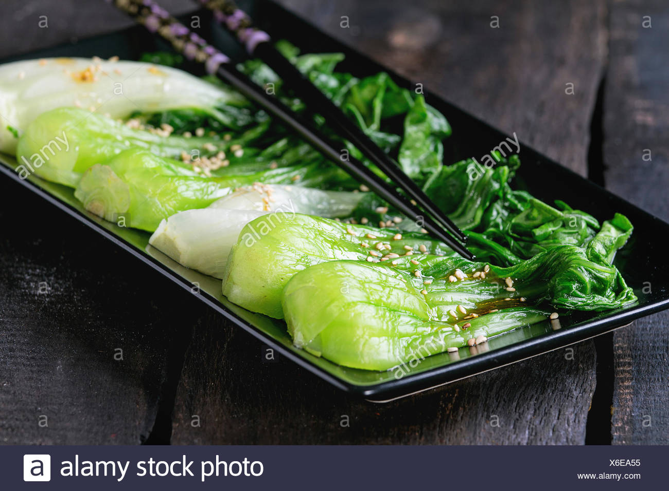 Cooked bok choy with sesame seeds and chili pepper olive oil in black square ceramic plate with black chopsticks over old wooden - Stock Image