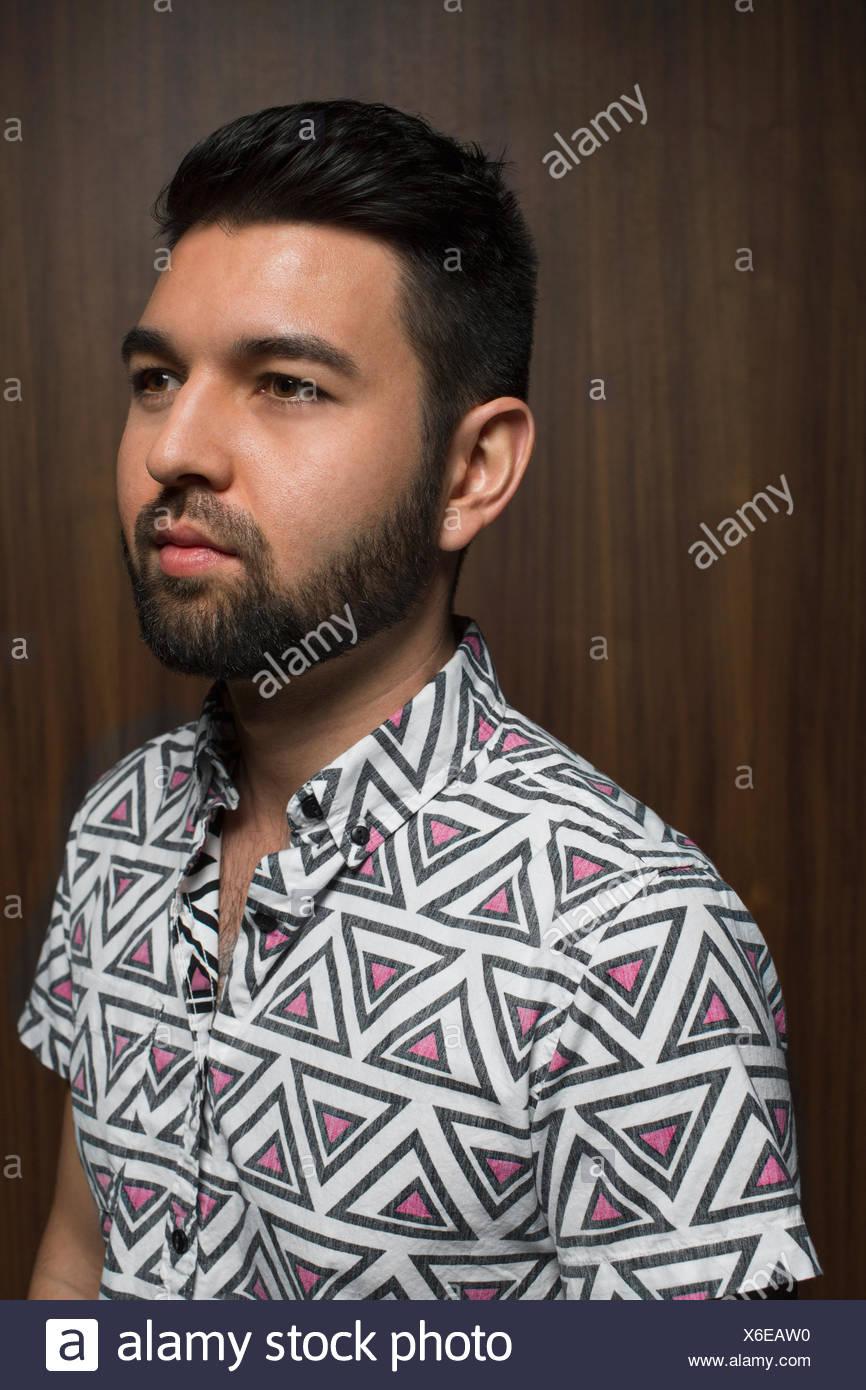 Portrait of pensive bearded man in geometric shirt - Stock Image