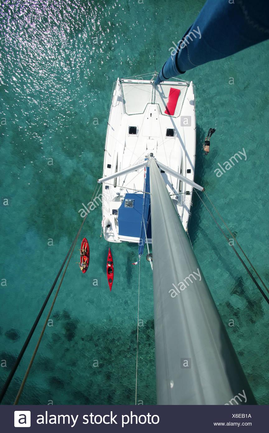 Kayak, snorkeler and open kayak viewed from the masthead of Moorings charter catamaran 'Pitch Pin', British Virgin Islands - Stock Image