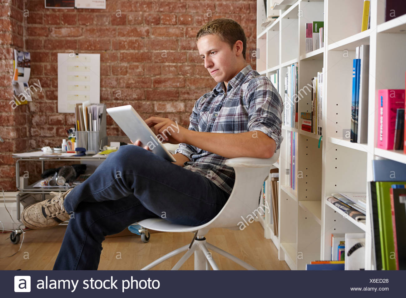 Young man sitting on chair using digital tablet - Stock Image