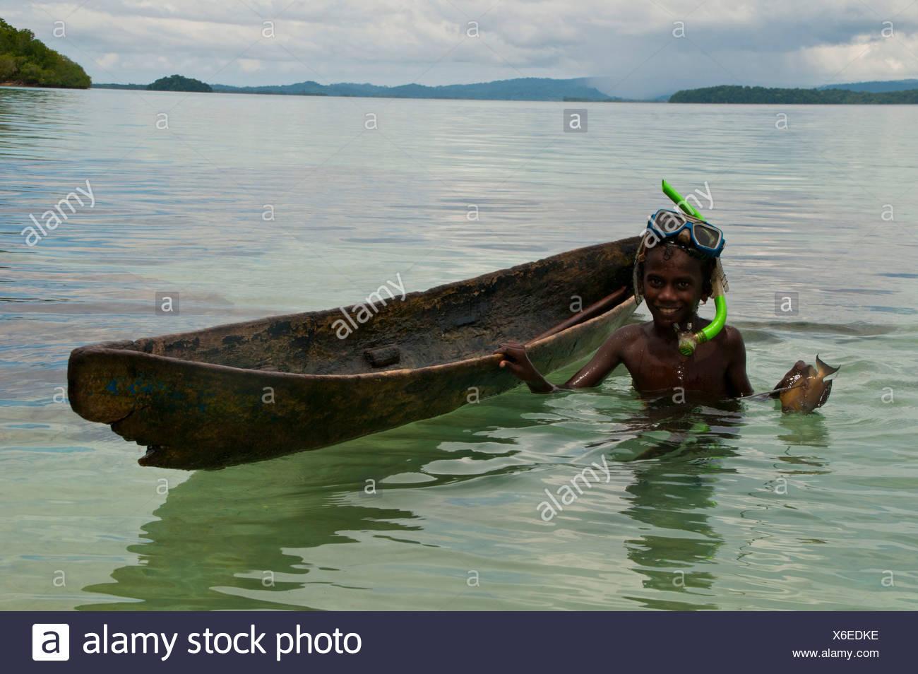 Boy fishing with his canoe and harpoon - Stock Image