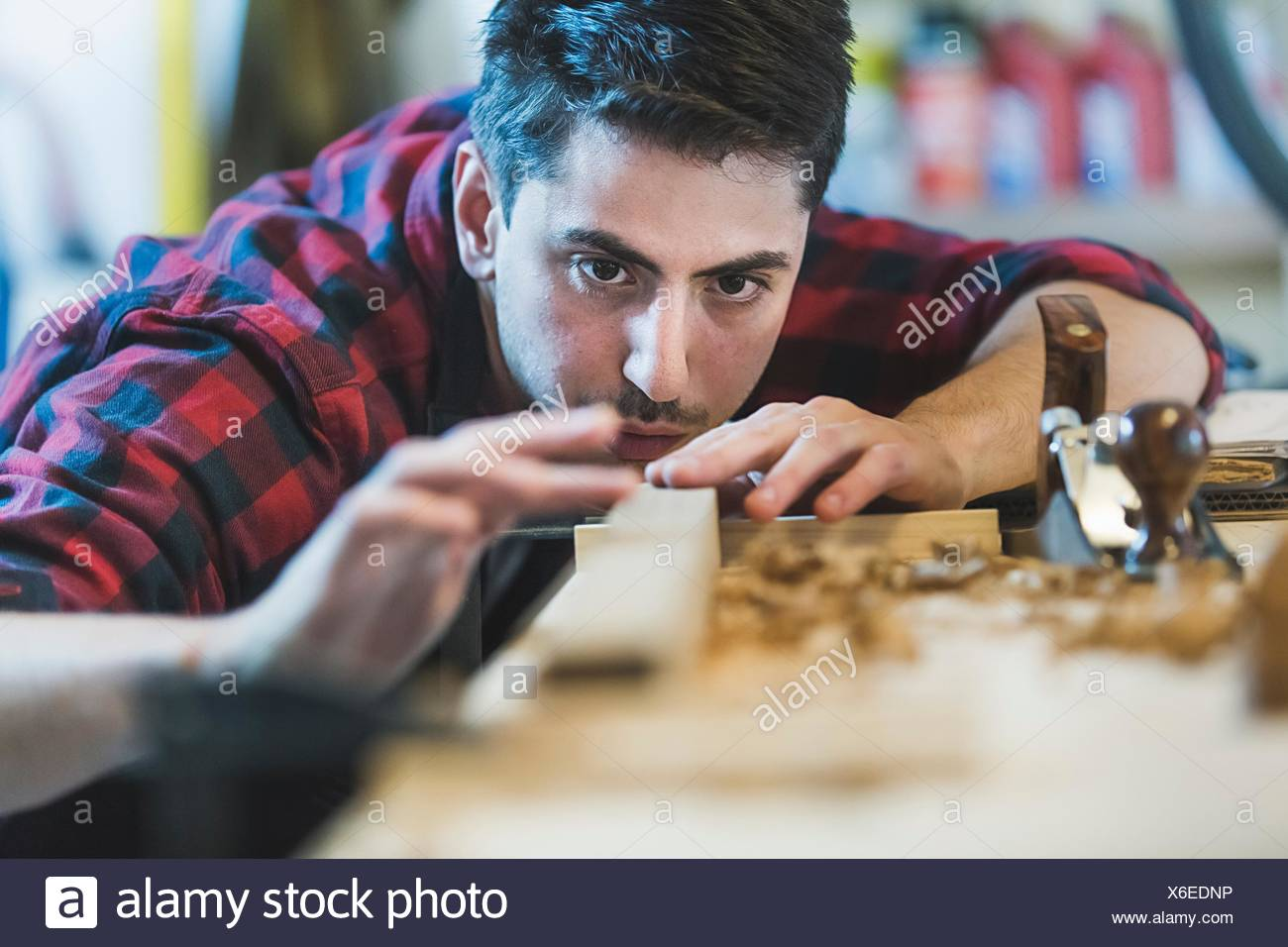 Young man using wood plane to smooth wood object - Stock Image