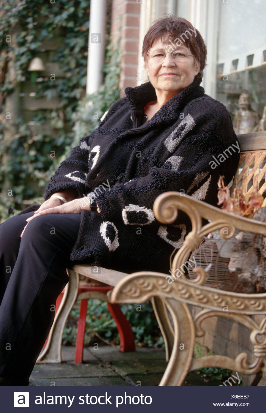 Senior woman sitting on front porch bench looking seriously at the camera  - SerieCVS500200d - Stock Image