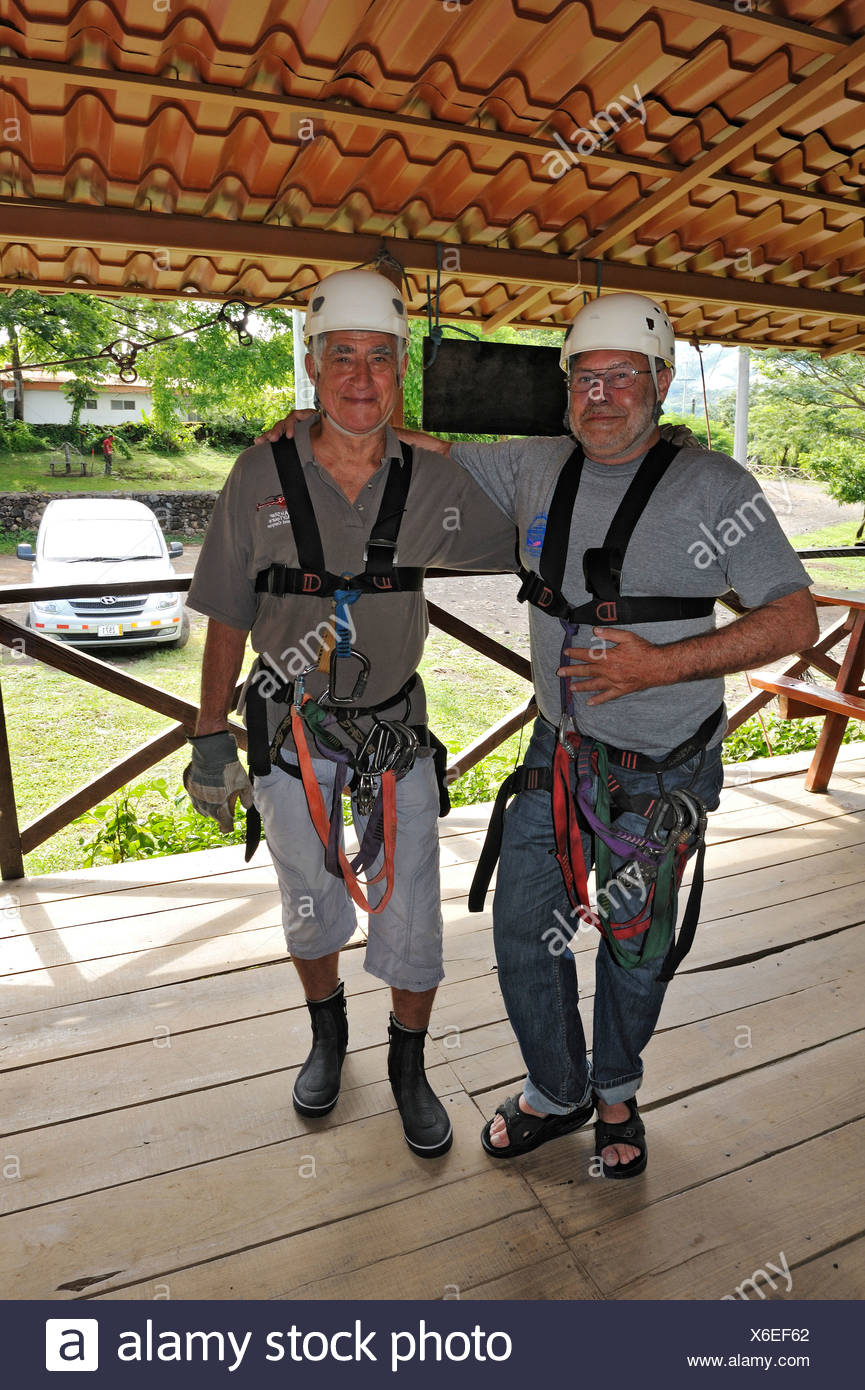 Two tourists, senior citizens, equipped for a canopy rope tour on the Hacienda Guachipelin near Liberia, Guanacaste Province - Stock Image