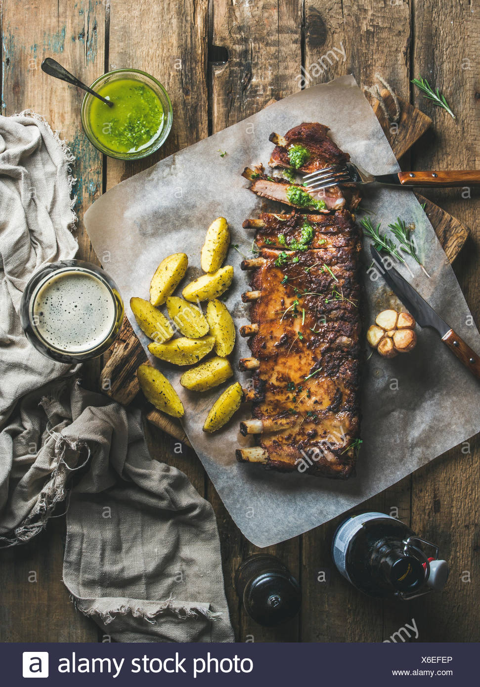 Roasted pork ribs with garlic, rosemary, green herb sauce, fried potato and dark beer on rustic wooden background, top view, ver - Stock Image