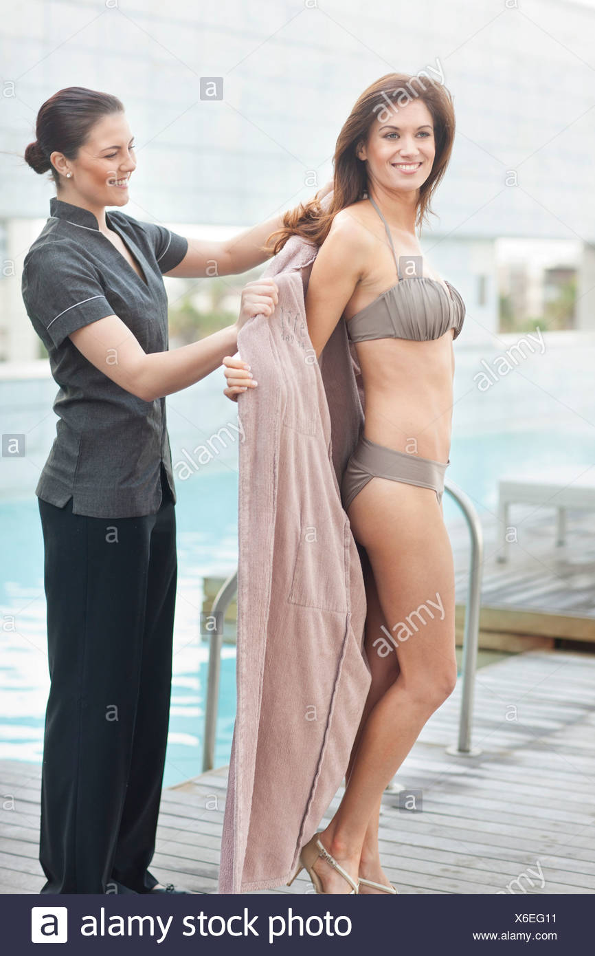 Service staff assisting woman at hotel poolside - Stock Image