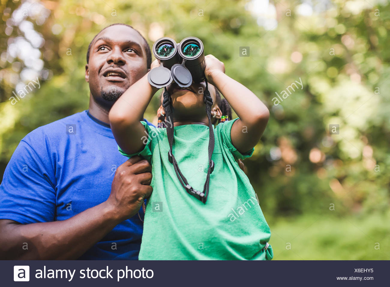 Young father and daughter bird watching in eco forest camp - Stock Image