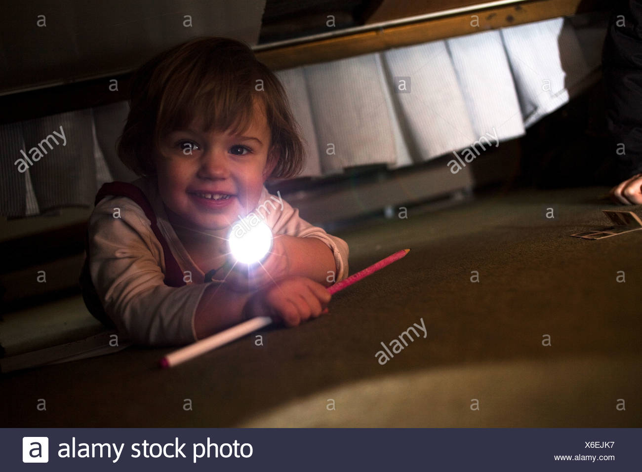 Young girl playing with torch underneath bed - Stock Image