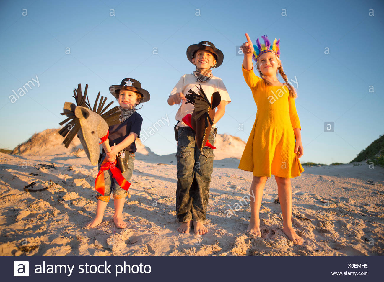 Sister and brothers dressed as native american and cowboys pointing from sand dunes - Stock Image