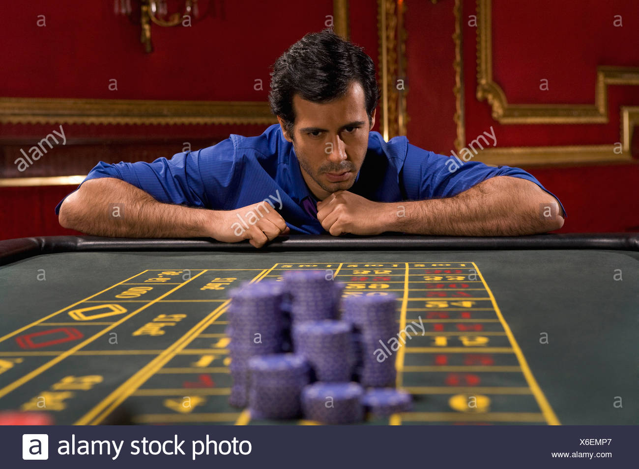 Anxious man looking bet on gaming table - Stock Image