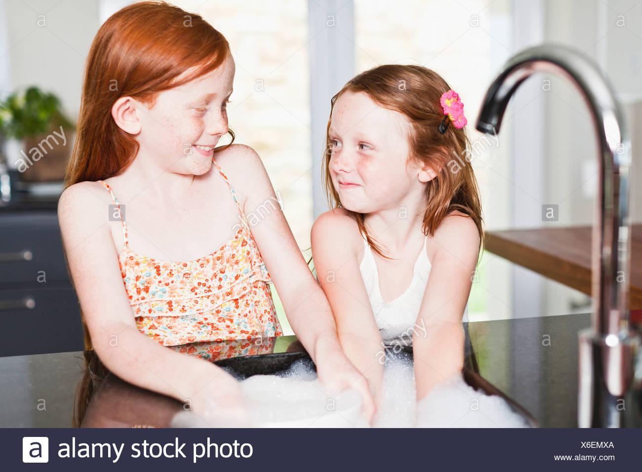 Smiling girls washing dishes in sink - Stock Image