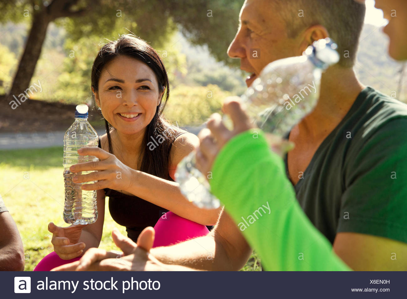 Mature male and female runners taking a water break in park - Stock Image
