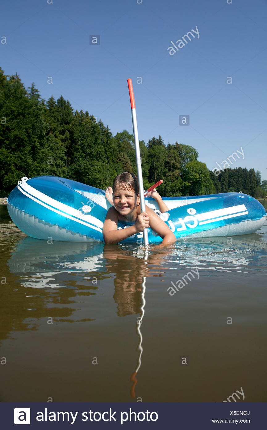 portrait of young boy in rubber boat on lake - Stock Image