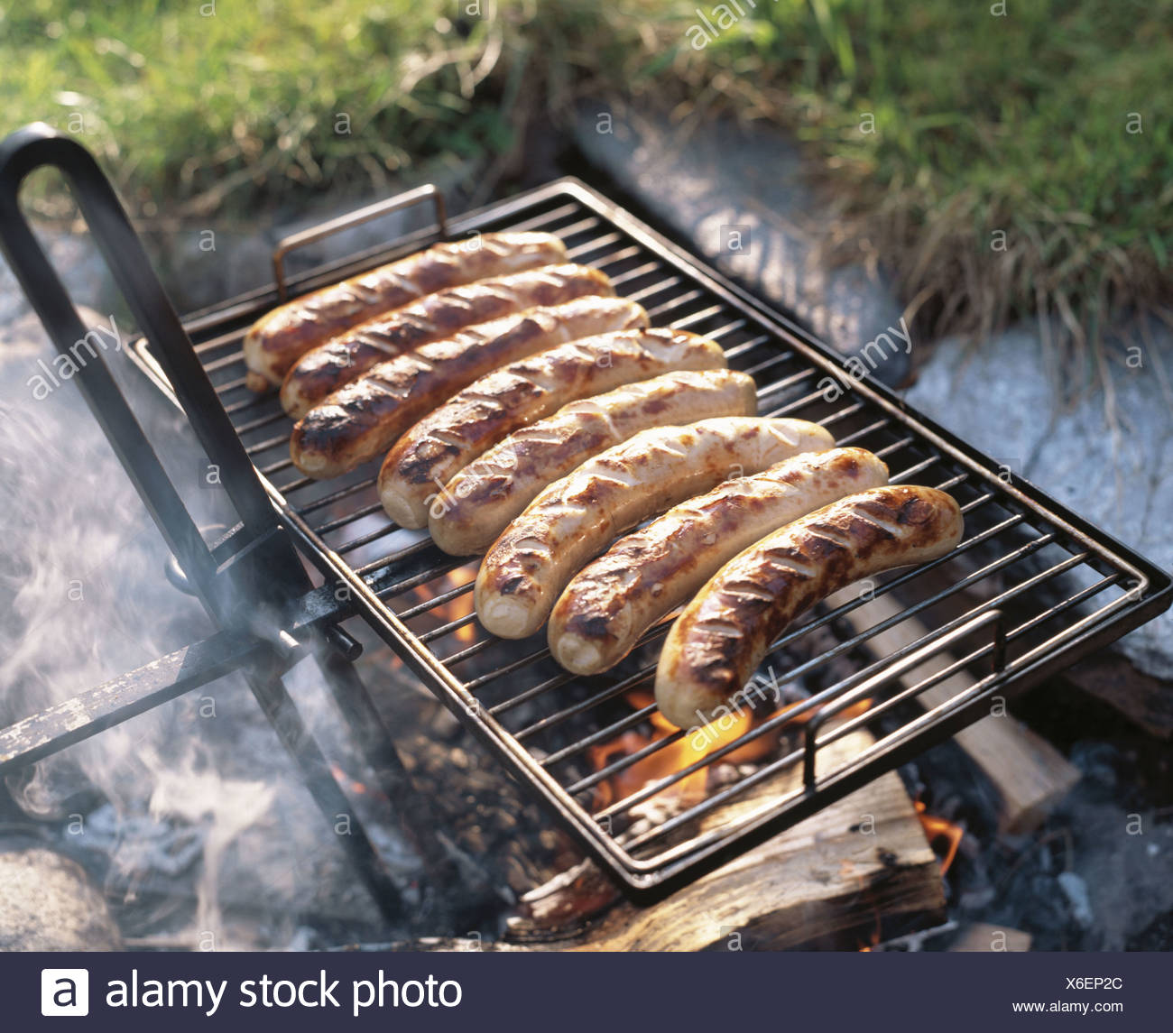 outside sausages fried sausages fireplace courts dishes grill barbecue grilling sausages - Stock Image