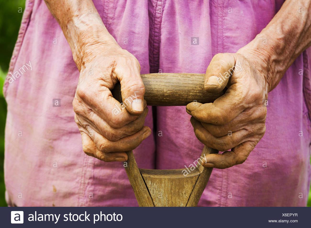 A woman holding a shovel on a farm. - Stock Image