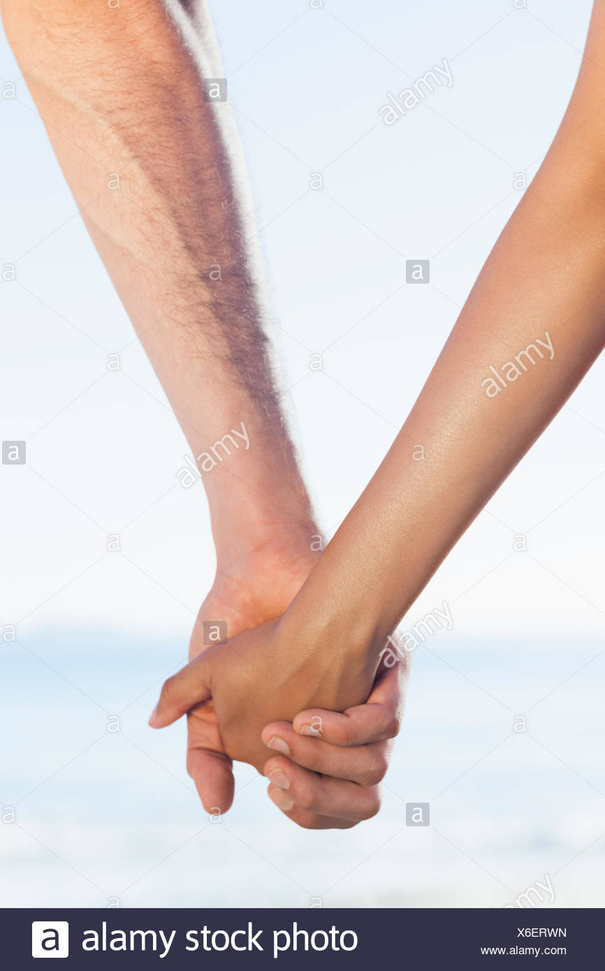 Loving young couple grasping hands - Stock Image