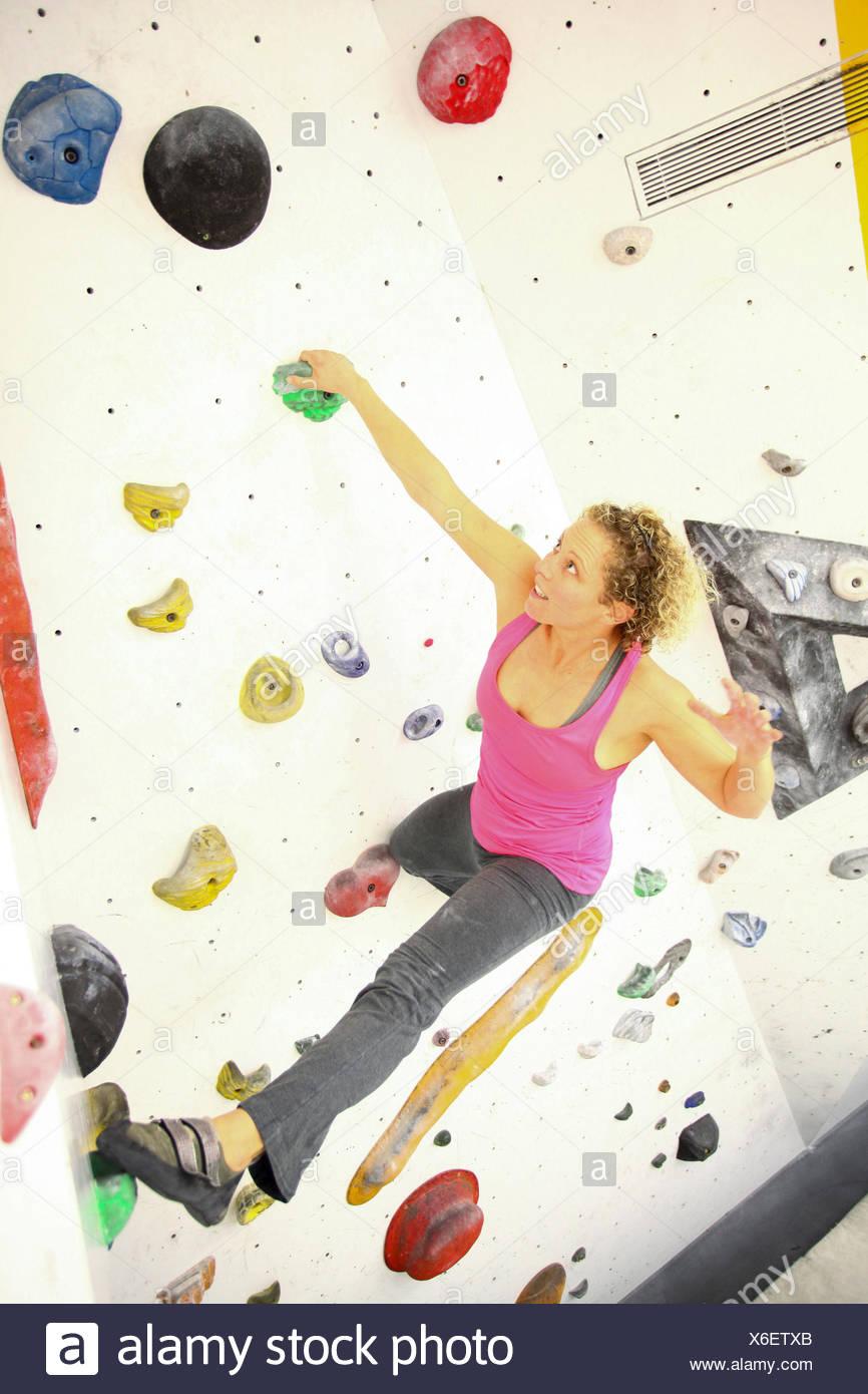 Woman climbing indoor artificial climbing wall - Stock Image