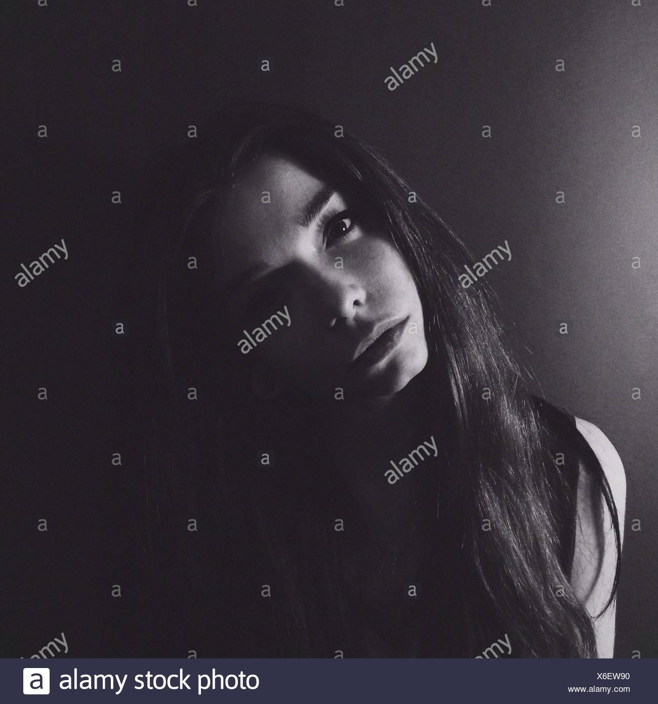 Close-Up Portrait Of A Serious Woman Over Plain Background - Stock Image