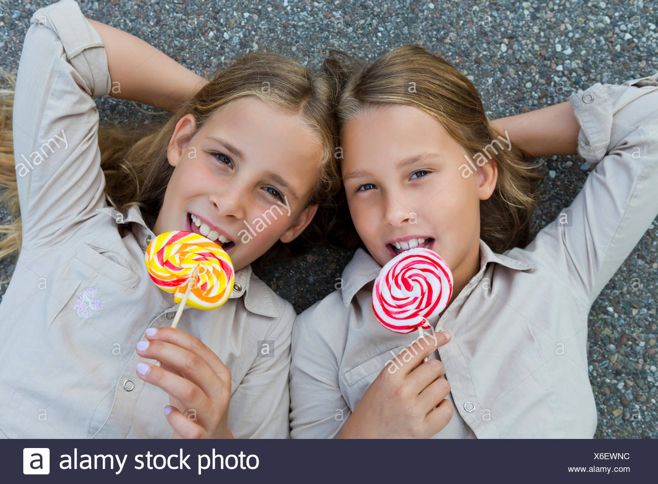 Twin girls, 9, lying on the floor with colourful lollipops - Stock Image