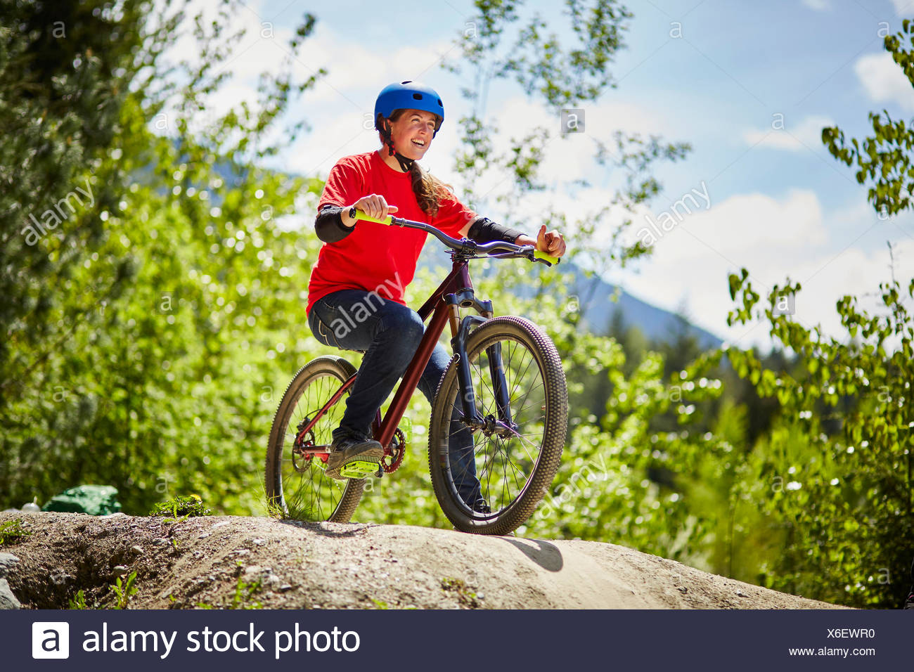 Young female bmx biker poised on edge of rock in forest - Stock Image