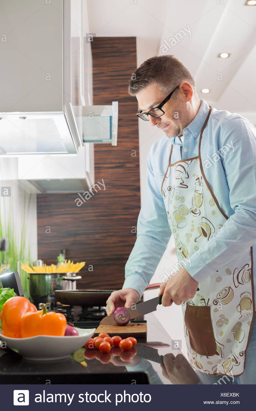 Mid-adult man cutting vegetables at kitchen counter - Stock Image