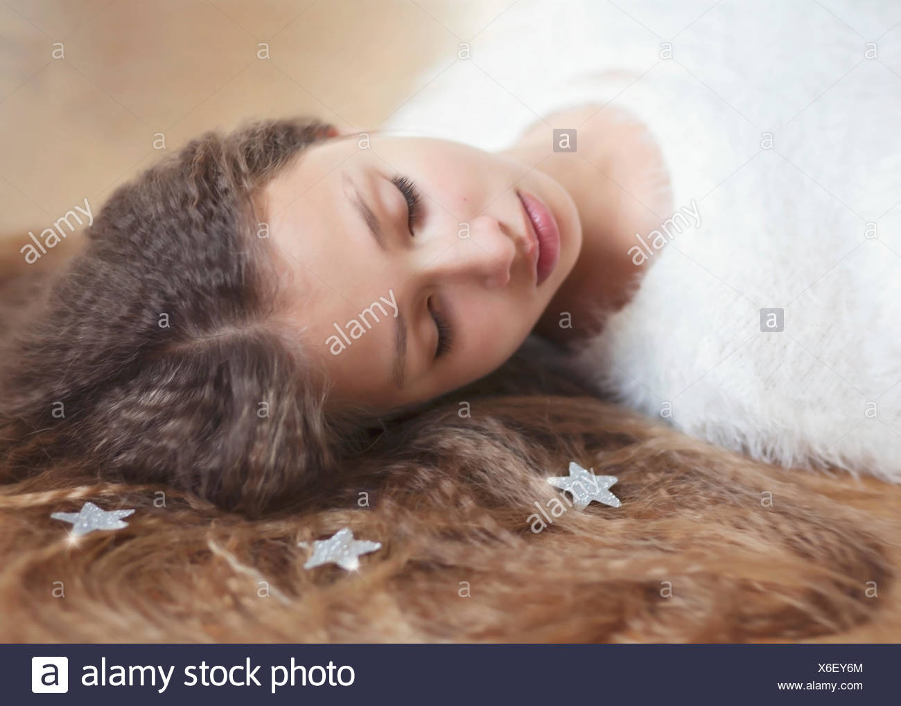 Portrait of girl (12-13) with long hair lying down - Stock Image
