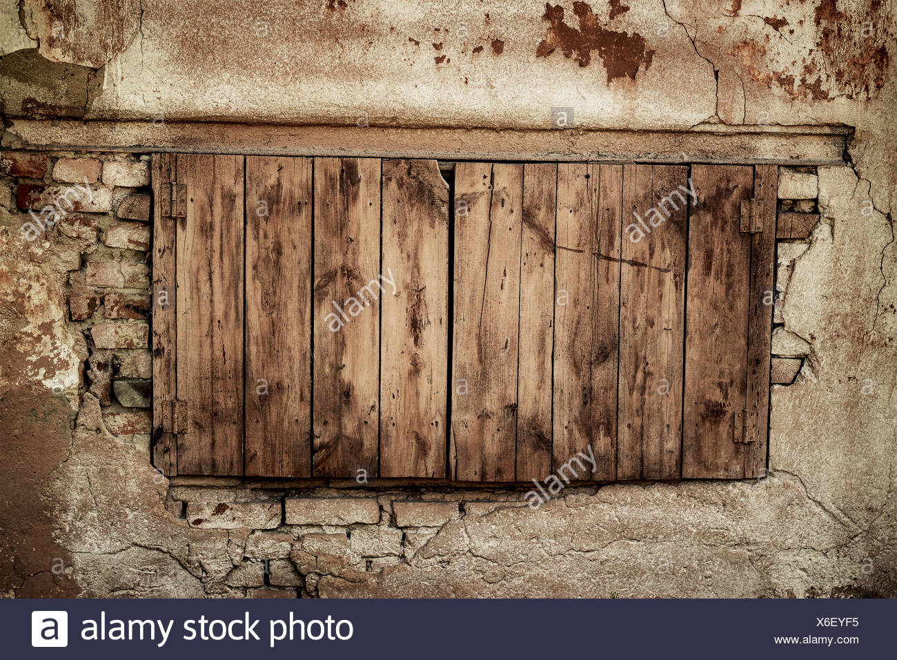 wall of an abandoned house with boarded up window - Stock Image