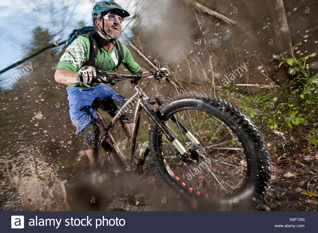 Mountain biker riding on a dirt road, Bavaria, Germany - Stock Image
