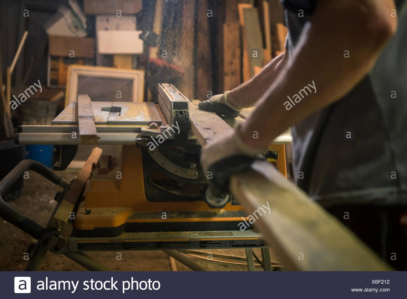 Wood artist in workshop, using woodworking machinery, mid section - Stock Image