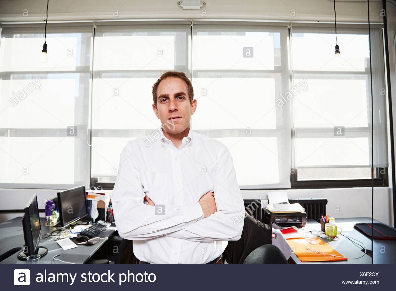 Mid adult man wearing white shirt in office - Stock Image